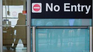 Symbolic image of Trump's travel ban; international travellers arriving at Boston's Logan Airport are reflected in a door next to a no entry sign (photo: Reuters/B. Snyder)