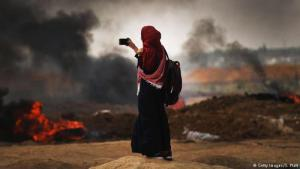 A Palestinian women records events at a protest in Gaza (photo: Getty Images/S. Platt)