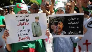 """Demonstrators protest on the streets of Algiers against army commander Gaid Saleh on 20 November 2019. Placards read """"He says he is for the protesters, but in fact he intends to preserve the status quo"""", """"They all must go: Gaid Saleh – Two faces of the same regime"""" (photo: picture-alliance/dpa/B. Bensalem)"""