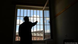 Prisoner in a cell standing looking out of the window (photo: picture-alliance/dpa)