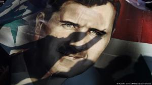 Shadows of Syrians are reflected on a giant poster showing President Bashar Assad, during a supporting rally in Damascus, Syria, Friday, 16 December 2011 (photo: AP Photo/Muzaffar Salman)