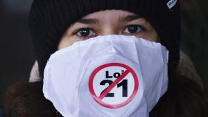 """A demonstrator displays her opinion outside the courthouse on the first day of the constitutional challenge to Bill 21, which bans public workers in positions of """"authority"""" from wearing religious symbols, before the Quebec Superior Court in Montreal on 2 November 2020 (photo: THE CANADIAN PRESS/Paul Chiasson)"""