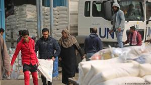 Palestinian refugees collect aid parcels at a United Nations food distribution centre in Khan Yunis in the southern Gaza Strip, January 2018 (photo: picture-alliance/Zuma/A. Amra)